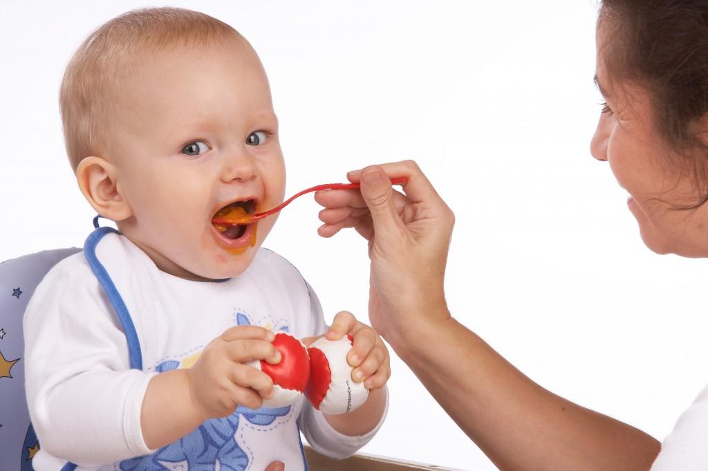 Mutter füttert ihr Kleinkind mit einem Löffel