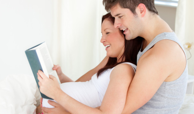 Portrait of a young pregnant woman and of her husband reading a book